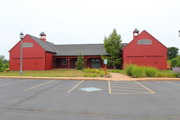 clinic front. building is red and shaped like a barn